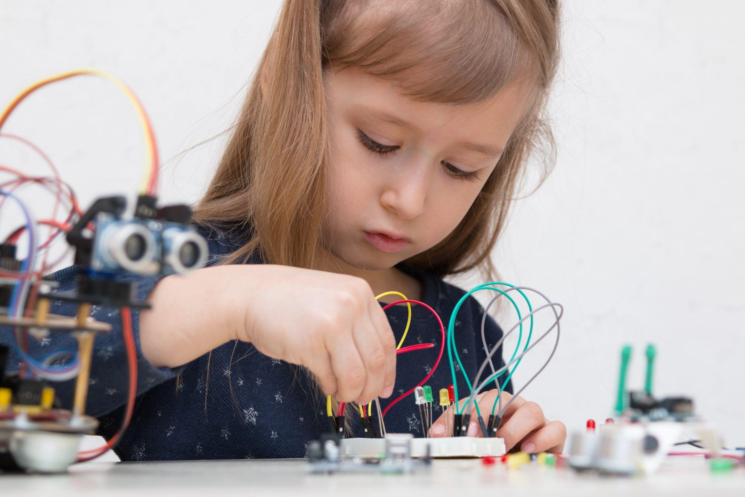 Girl interacting with machine - Learning micro bit coding-min