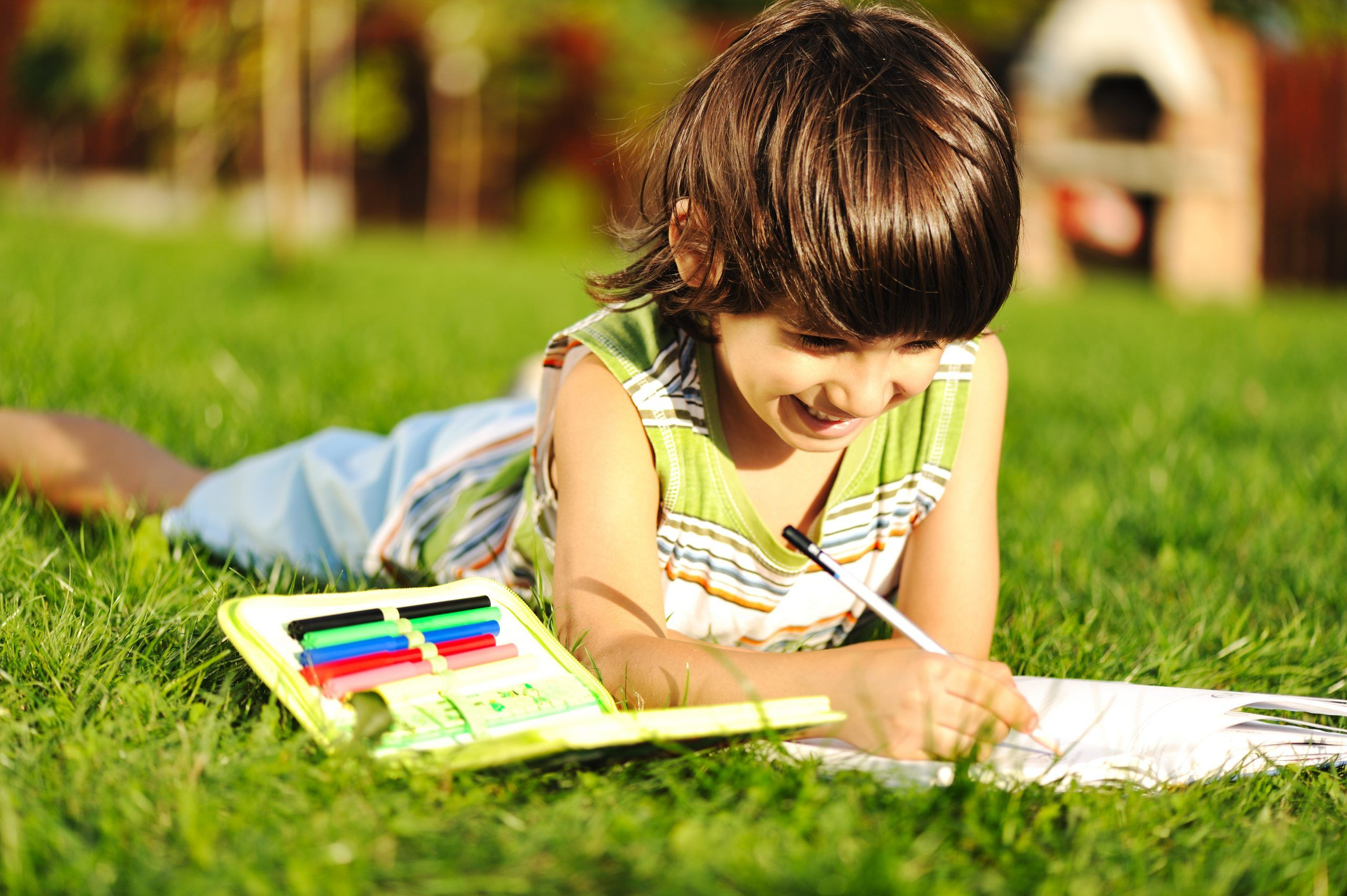 Young,Boy,Outdoors,On,The,Grass,Reading,A,Book,,Writting